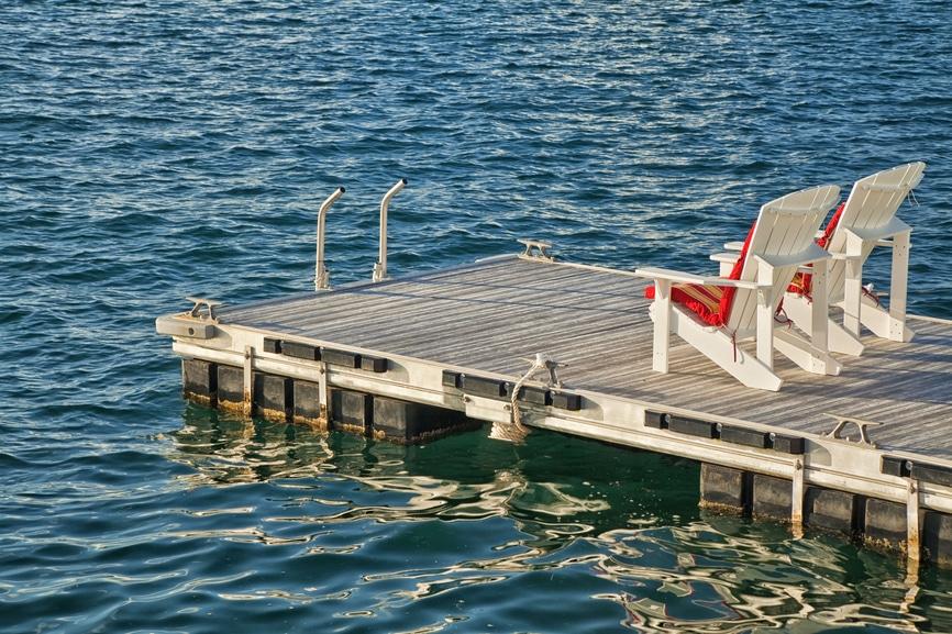 2 Sessel auf einem Holzsteg über dem Wasser