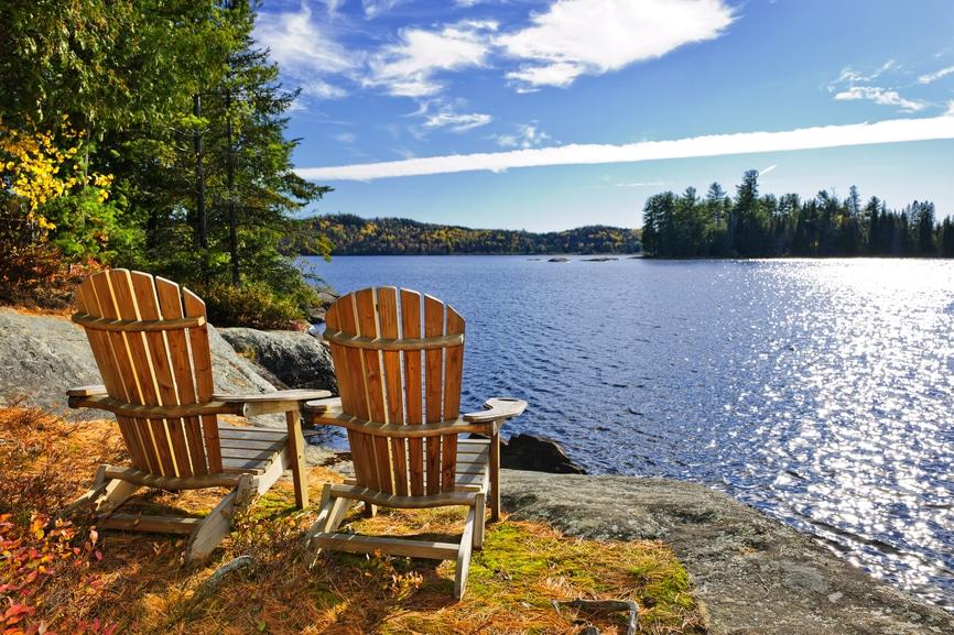 Holzsessel am See, welcher von Bäumen umgeben ist