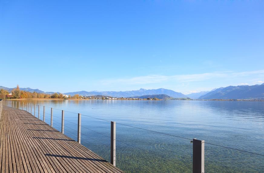 Holzsteg dem See entlang, im Hintergrund die Berge
