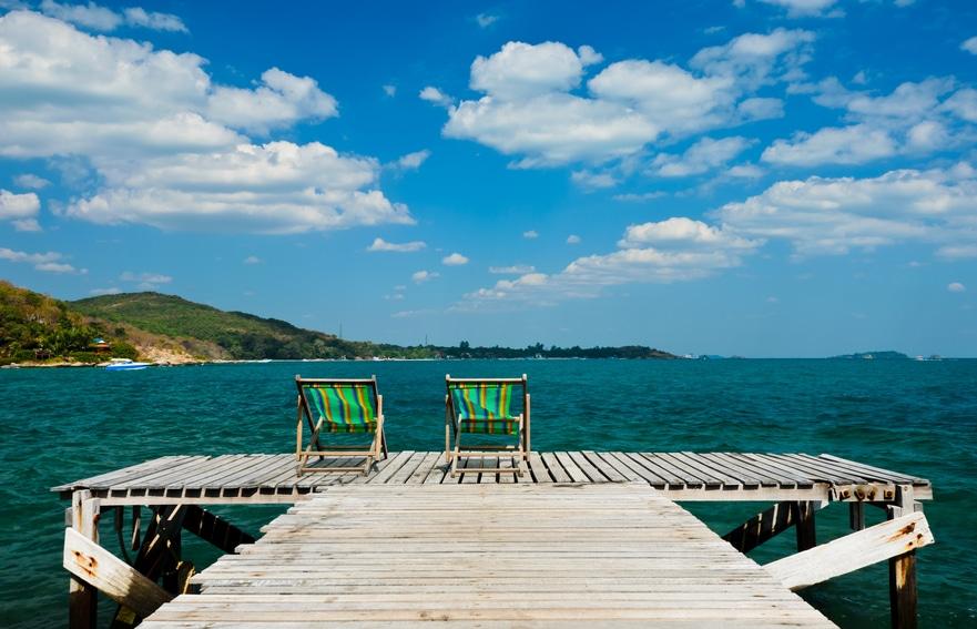 Sessel auf Holzdeck mit Sicht auf's Wasser