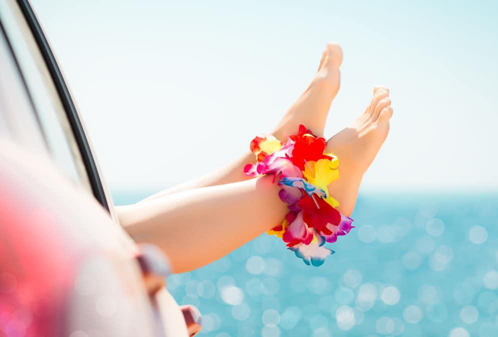 Frauenfüsse baumeln aus einem Autofenster. Im Hintergrund glitzert das Meer.